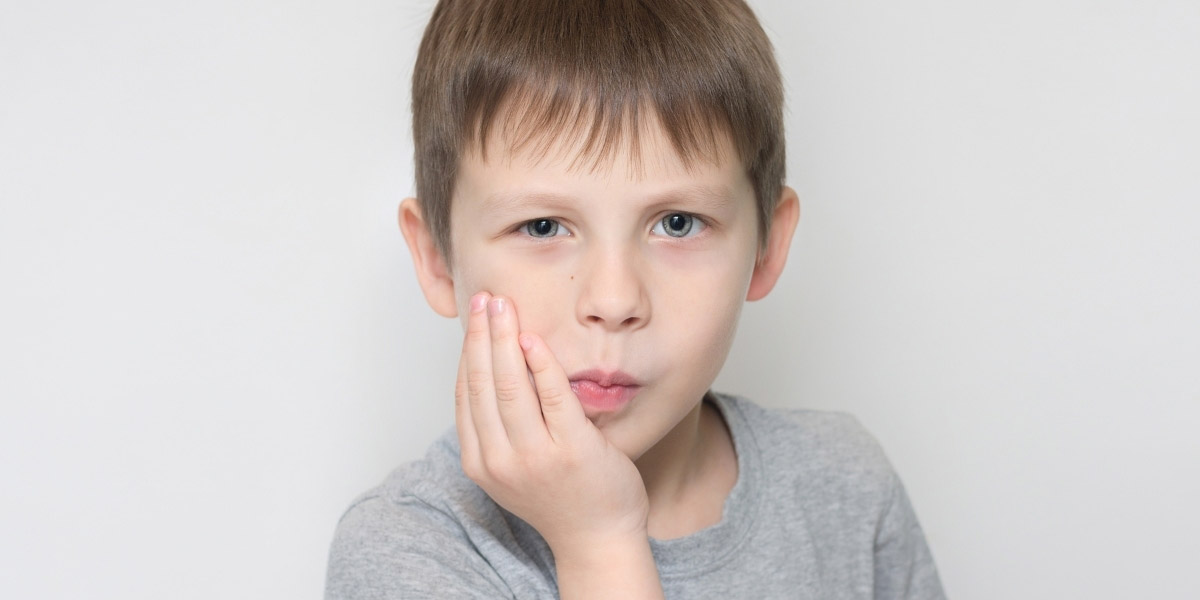 Kid holding jaw in pain